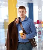 Young office worker arriving to modern office. At morning holding coffee Royalty Free Stock Photography