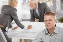 Young office worker with colleagues in background Royalty Free Stock Photography