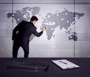 Business person drawing dots on world map. A young office worker drawing on world map and connecting dots with lines, presenting marketing sterategy at office Royalty Free Stock Photo