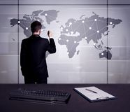 Business person drawing dots on world map. A young office worker drawing on world map and connecting dots with lines, presenting marketing sterategy at office Royalty Free Stock Image