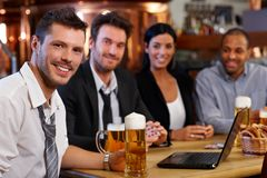 Young office worker drinking beer at pub Stock Images