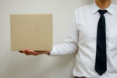 Young office worker holding an empty paper box Royalty Free Stock Photography