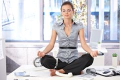 Young office worker meditating on top of desk Stock Images