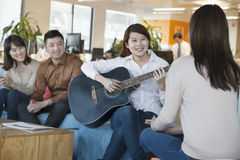 Young Office Worker Playing Guitar to Colleagues Royalty Free Stock Photography