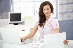 Young office worker smiling in bright office Royalty Free Stock Photo