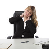 Young office worker with a stiff neck. Pretty young female office worker with a stiff neck stretching and grimacing as she sits at her desk Stock Photo