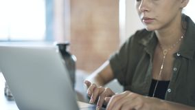 Young office worker typing and using touchpad at work. Beautiful young office worker is typing and using her laptop touchpad at work. Handheld real time medium stock footage