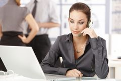 Young office worker using headset sitting at desk. Young female office worker sitting at desk, using headset, others talking in background Stock Photos