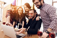 Young office workers looking at laptop screen together. They have glasses with champagne in their hands. They are in a good mood Royalty Free Stock Images