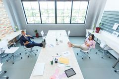 Young office workers, the lunch break business put their feet on the table. Royalty Free Stock Image