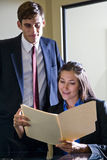 Young office workers reviewing folder Royalty Free Stock Images