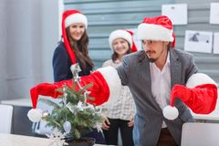 Young office workers in Santa`s hats have fun Stock Images