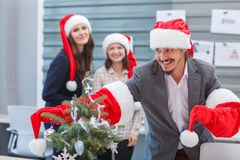 Young office workers in Santa`s hats have fun Stock Photo