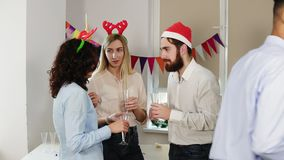Young office workers talking and holding glasses with sparkling wine during christmas party in the office while their