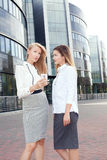 Young office workers talking, working. Couple of young beautiful businesswoman talking outdoor. Outdoor photo. Sunny day. Office building on background stock image