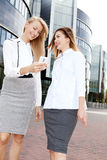 Young office workers talking, working. Couple of young beautiful businesswoman talking outdoor. Outdoor photo. Sunny day. Office building on background royalty free stock images