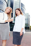 Young office workers talking, working. Couple of young beautiful businesswoman talking outdoor. Outdoor photo. Sunny day. Office building on background royalty free stock photos