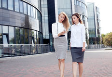 Young office workers talking, working. Couple of young beautiful businesswoman talking outdoor. Outdoor photo. Sunny day. Office building on background royalty free stock photo