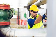 Oil worker closes the valve on the oil pipeline stock photos