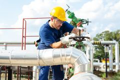 Oil worker is turning valve on the oil pipeline. Young Oil worker is turning valve on the oil pipeline stock photo