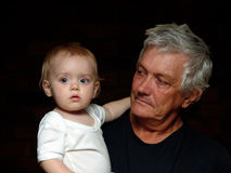 Young and Old. My daughter and her grandfather against a dark background wearing black and white Stock Photography