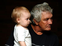 Young and Old. My daughter and her grandfather against a dark background wearing black and white royalty free stock photo