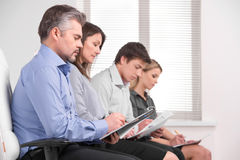 Young and old business people sitting in a row. Writing down and listening in modern office stock photography