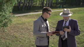 Young and old businessmen speaking and working with tablet on the street. 4K stock footage