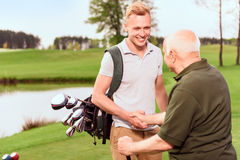 Young and old golf players shaking hands. Nice job. Young and old golf players standing on golf course with golf equipment and shaking hands Stock Photography