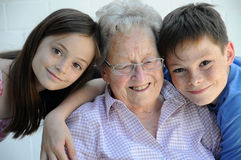 Young and old. Grandchildren embracing  their ninety years old grandmother Stock Images