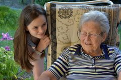 Me and grandma, girl surprises her great-grandma. Young and old, granddaughter with her  ninety years old great- grandmother Stock Image
