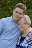 Boy embraces lovingly his great-grandma stock images