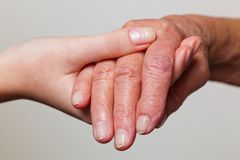 Young and old hand with a walking cane Stock Photography