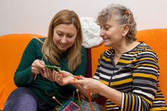 Young and old while knitting. Young and old knitting and crocheting together Royalty Free Stock Images