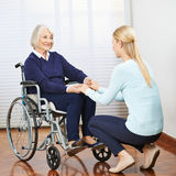Young and old woman holding hands. Young and old women in wheelchair holding hands in a nursing home stock photography