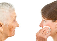 Young and old. Old women wiping off the face of a young one with a makeup pad royalty free stock photography