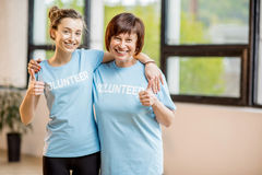 Young and older volunteers indoors. Portrait of an older and young female volunteers in blue t-shirts standing together at the office royalty free stock photography