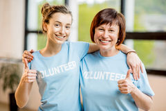 Young and older volunteers indoors. Portrait of an older and young female volunteers in blue t-shirts standing together at the office Royalty Free Stock Photos