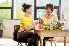 Young and older women with healthy food indoors. Young and older women sitting with healthy food and fresh drinks after the sports training indoors on the window Royalty Free Stock Photos