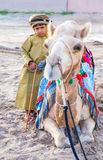 Young Omani boy dressed in traditional clothing. Muscat, Oman - Feb 4, 2017: Young Omani boy dressed in traditional clothing posing next to his camel Royalty Free Stock Photo
