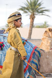 Young Omani boy dressed in traditional clothing. Muscat, Oman - Feb 4, 2017: Young Omani boy dressed in traditional clothing posing next to his camel Stock Image