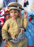 Young Omani boy dressed in traditional clothing. Muscat, Oman - Feb 4, 2017: Young Omani boy dressed in traditional clothing posing next to his camel Royalty Free Stock Photography