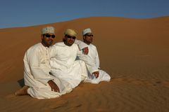 3 young, modern omani men at Wahiba Sands Royalty Free Stock Image