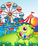 A young one-eyed monster holding a balloon near the carnival. Illustration of a young one-eyed monster holding a balloon near the carnival Royalty Free Stock Photo