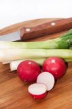 Young onions and chopped radishes on the wooden board.  Royalty Free Stock Photos