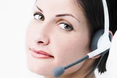 Young operator. Beautiful young woman with charming big green eyes is receiving calls on a headset royalty free stock image