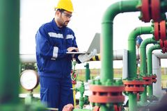 Operator recording operation of oil and gas process at oil and rig plant. Young Operator recording operation of oil and gas process at oil and rig plant stock photos