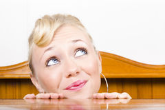 Young, optimistic Caucasian woman stares upwards from behind a c Stock Photos