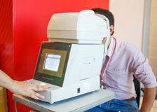 Young Optometrist measuring patient's eye pressure with tonomete Royalty Free Stock Photography