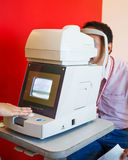 Young Optometrist measuring patient's eye pressure with tonomete Royalty Free Stock Image